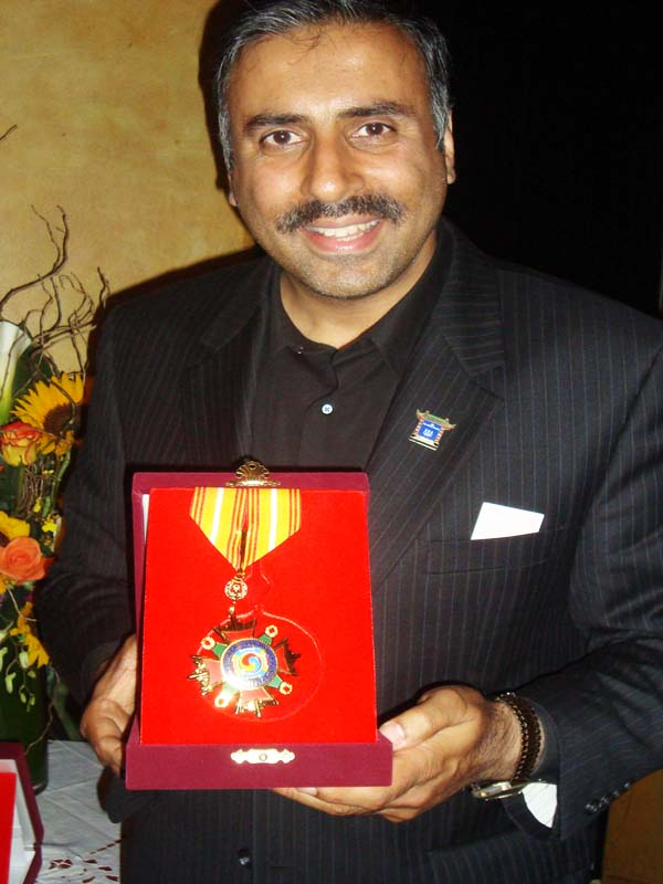 Dr.Abbey holding up KPOW Medal