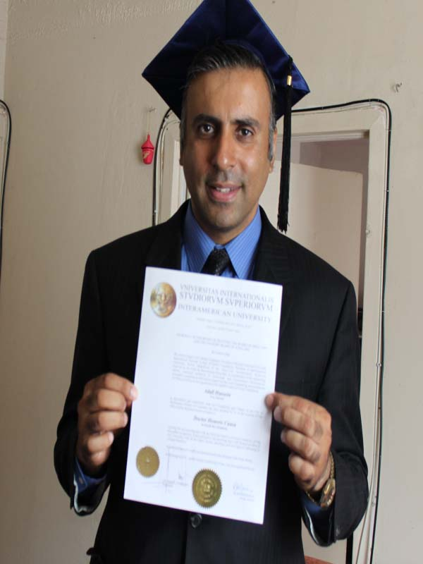 Dr.Abbey holding up Phd Degree
