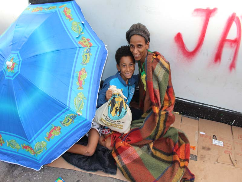 Mother and son living on the street under an umbrella